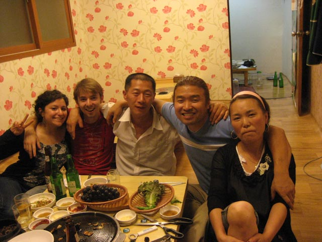 4 people posing for a camera at a dinner table