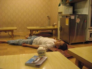 a korean man passed out on the fllor of a restaurant from too much alcohol and food