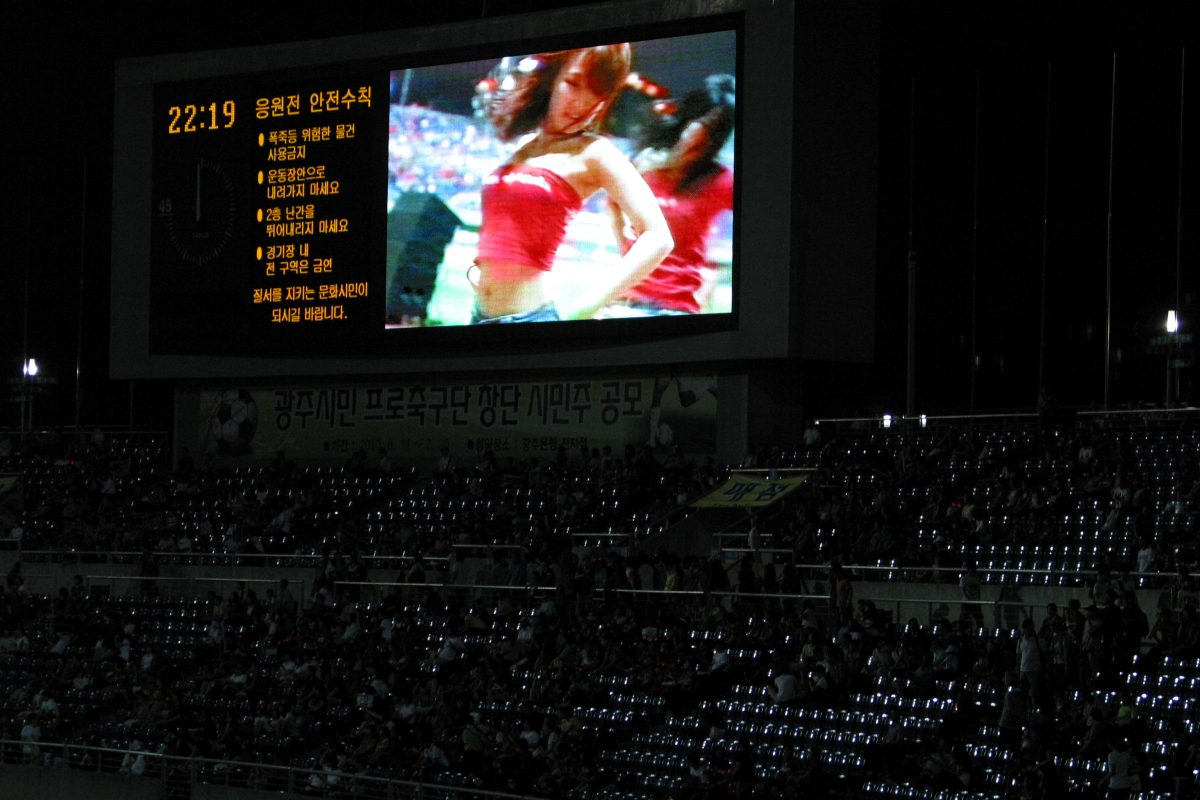 a picture of a cheerleader on a screen at a stadium