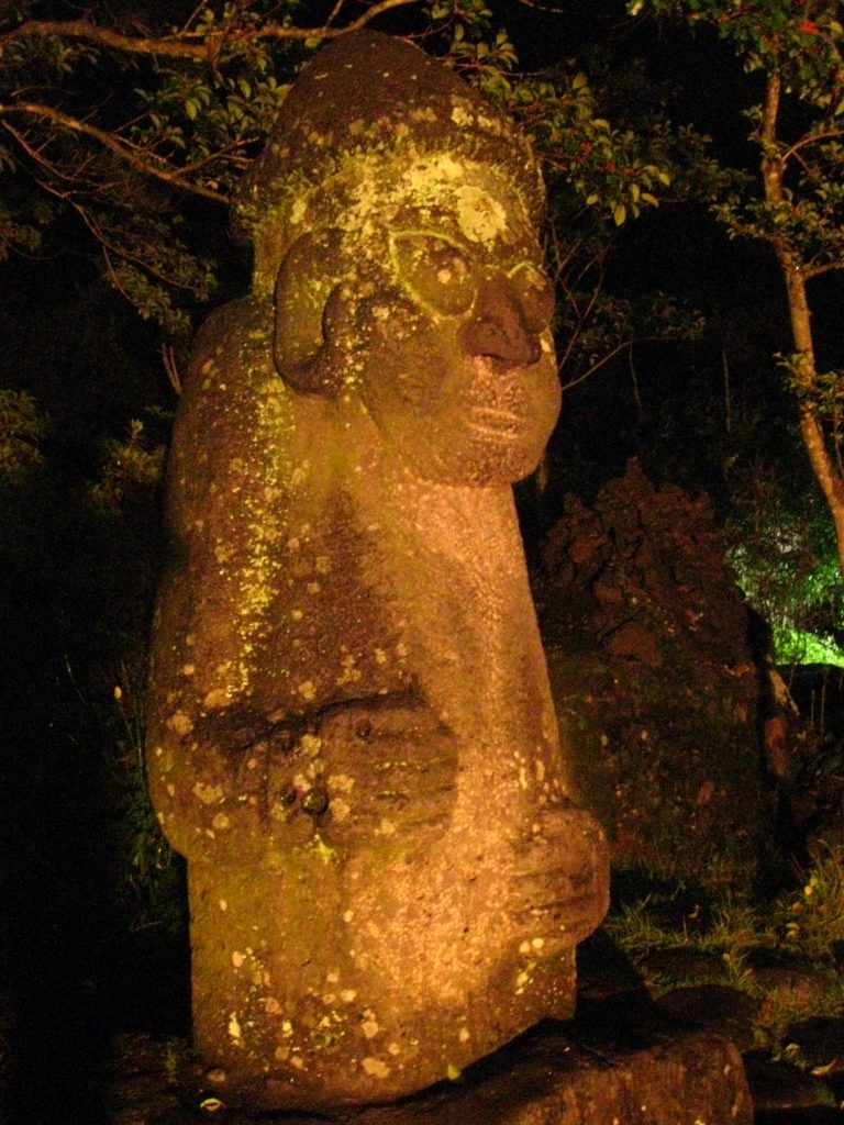 an orange hue photo of a stone statue called a Dolharubang