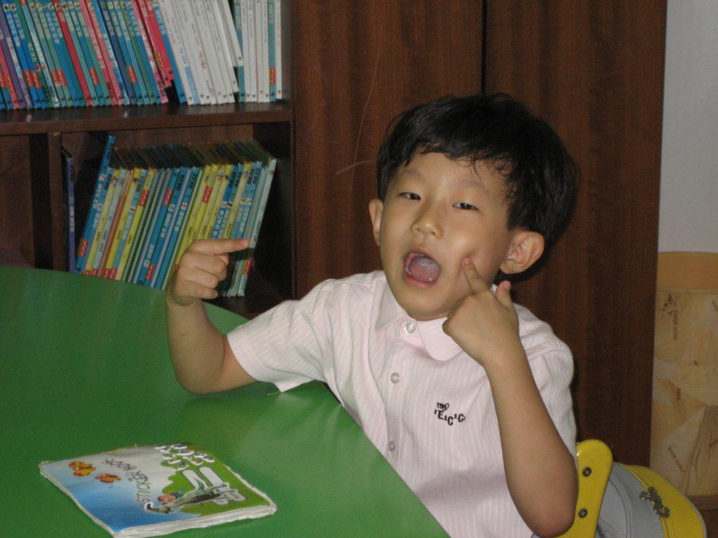 a korean child poking his cheeks