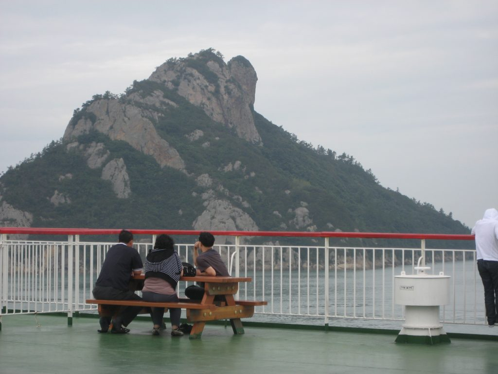 people sitting at a picnic table on a ferry boat