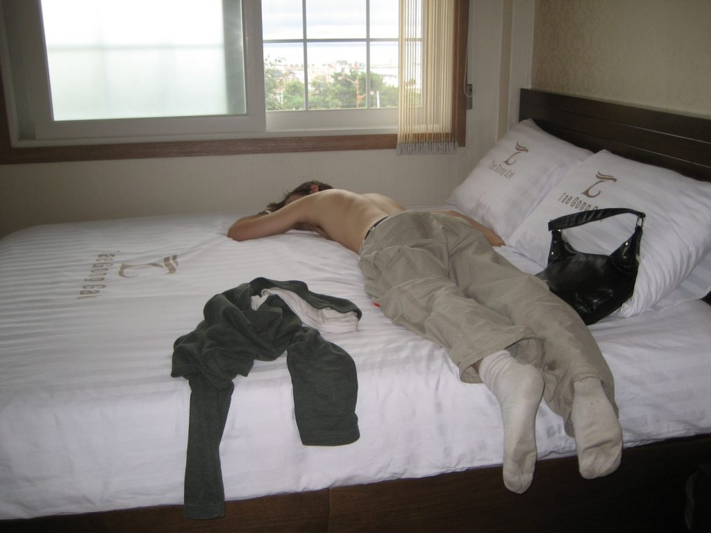 a young man passed out face down on a bed, weary from travel